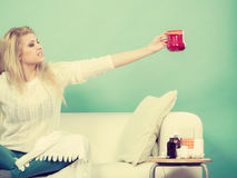 Happy woman showing cup of tea Royalty Free Stock Photos