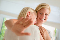 Happy woman showing engagement ring to mother Stock Photo