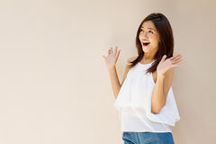 Happy woman showing exciting positive expression. With blank background, warm tone brown beige color Stock Image