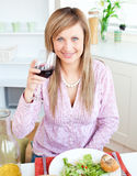 Happy woman showing glass of red wine Royalty Free Stock Image
