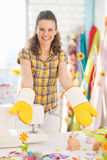 Happy woman showing hand made pot holder mitts Royalty Free Stock Image
