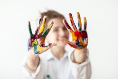 Happy woman showing hands painted in colorful paints. On white background. Fun concept stock images
