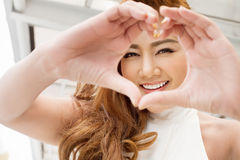 Happy woman showing heart hand sign to you Royalty Free Stock Image