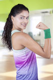 Happy woman showing her bicep at gym Stock Photography