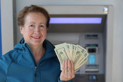 Happy woman showing her money at an ATM. Woman showing her money at an ATM Royalty Free Stock Image