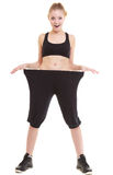 Happy woman showing how much weight she lost, big pants Royalty Free Stock Images