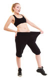 Happy woman showing how much weight she lost, big pants. Weight loss, healthy lifestyle. Full length blonde young happy funny woman fitness girl with big pants Royalty Free Stock Photo