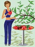 Happy woman showing how much weight she lost. Next to a table  full of fruits and vegetables  and green tree Stock Photos