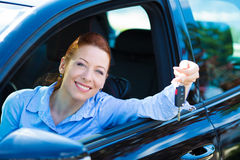 Happy woman showing keys from her new car. Closeup portrait happy, smiling, young, attractive woman, buyer sitting in her new black car showing keys isolated Royalty Free Stock Photo