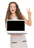 Happy woman showing laptop and victory gesture Royalty Free Stock Image
