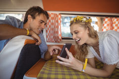 Happy woman showing mobile phone to man in van Royalty Free Stock Photos
