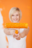 Happy woman showing paint roller Royalty Free Stock Image