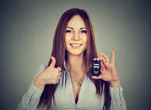 Happy woman showing remote car keys and thumbs up Royalty Free Stock Photo