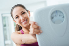 Happy woman showing a scale Stock Photography
