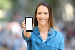 Happy woman showing smart phone mock up. Front view of a happy woman showing smart phone screen mock up in the street royalty free stock photography