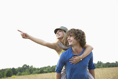 Happy woman showing something while enjoying piggyback ride on man in field. Happy women showing something while enjoying piggyback ride on men in field Royalty Free Stock Photography