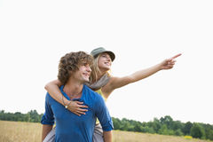Happy woman showing something while enjoying piggyback ride on man in field. Happy women showing something while enjoying piggyback ride on men in field royalty free stock images