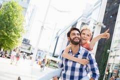Happy woman showing something to man while enjoying piggyback ride in city Stock Image