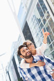 Happy woman showing something to man while enjoying piggyback ride in city Royalty Free Stock Photography