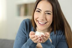 Happy woman showing sugar cubes to camera. Sitting on a couch in the living room at home Royalty Free Stock Photo