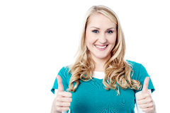 Happy woman showing thumb up sign by two hands. Gorgeous young woman showing double thumbs up Stock Images