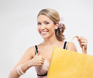 Happy woman showing thumbs up and holding a shopping bag Stock Photo