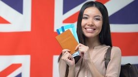 Happy woman showing tickets and passport, English flag, travelling to Britain. Stock footage stock footage
