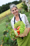 Happy woman showing vegetables from garden Royalty Free Stock Images