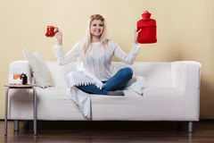 Woman showing ways to get rid of fever. Happy woman showing ways to get rid of fever holding hot water bottle and hot drink in mug sitting, relaxing on couch Stock Images