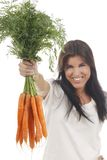 Happy woman shows on a bunch of carrots. Happy woman with a bunch of carrots isolated on white stock image