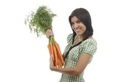 Happy woman shows on a bunch of carrots. Happy woman with a bunch of carrots isolated on white stock photography