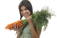 Happy woman shows on a bunch of carrots. Happy woman with a bunch of carrots isolated on white royalty free stock photography