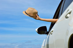 Happy woman shows sun hat from car window. Woman shows sun hat from car window Stock Image
