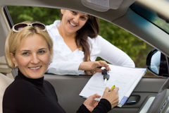 Happy woman signing for her new car. Happy beautiful blond women signing for the purchase her new car with the smiling saleslady holding the contract through the Royalty Free Stock Image