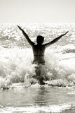 Happy woman silhouette. Silhouette of a wet young woman in a waving sea Royalty Free Stock Images