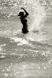 Happy woman silhouette. Silhouette of a wet young woman in a waving sea splashing the water, vertical Stock Photo