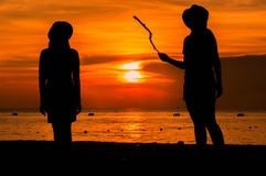 Happy woman silhouette standing against sunset with arms raised. Up Stock Image