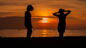 Happy woman silhouette standing against sunset with arms raised. Up Stock Images