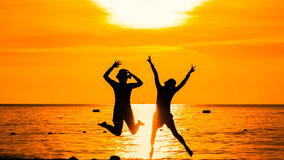 Happy woman silhouette standing against sunset with arms raised Royalty Free Stock Images