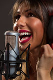 Happy Woman Singer In Front Of The Microphone Stock Image