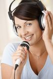 Happy woman singing at home Stock Photo