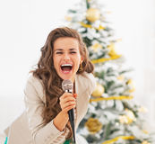 Happy woman singing with microphone in front of christmas tree Royalty Free Stock Images