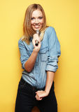 Happy woman singing in microphone over yellow background Royalty Free Stock Image
