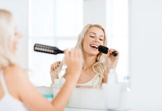 Happy woman singing to hair brush at bathroom Stock Images