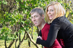 Happy woman sits on back of man and laughs in park Stock Photos