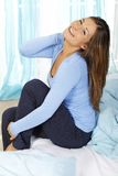 Happy woman sits on her bed. Smiling looking up stock photography