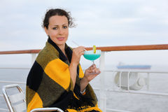 Happy woman sits and holds cocktail. Happy woman wrapped in plaid sits on chair on cruise liner deck and holds cocktail Royalty Free Stock Images