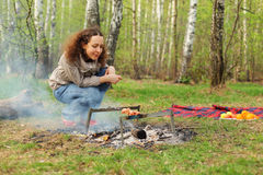 Happy woman sits near campfire with grill royalty free stock photography