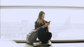 Happy woman sits with smartphone by airport window. Caucasian girl with backpack using messenger app in terminal. 4K. Royalty Free Stock Photography