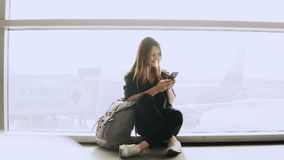 Happy woman sits with smartphone by airport window. Caucasian girl with backpack using messenger app in terminal. 4K. Happy woman sits with smartphone by royalty free stock photo